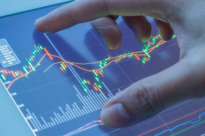 Mężczyzna dotyka ekranu, na którym wyświetlają się wykresy na rynku forex waluty
